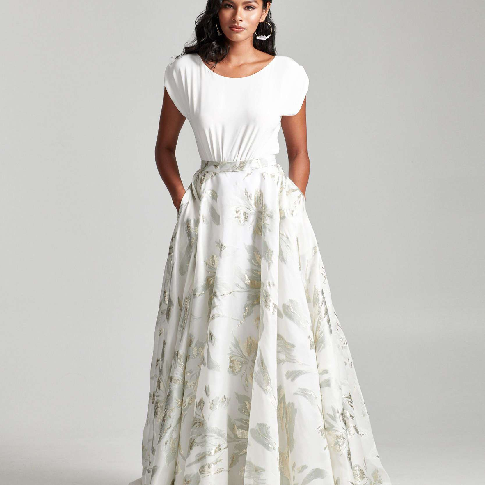 Model in short-sleeve white top with floral printed skirt