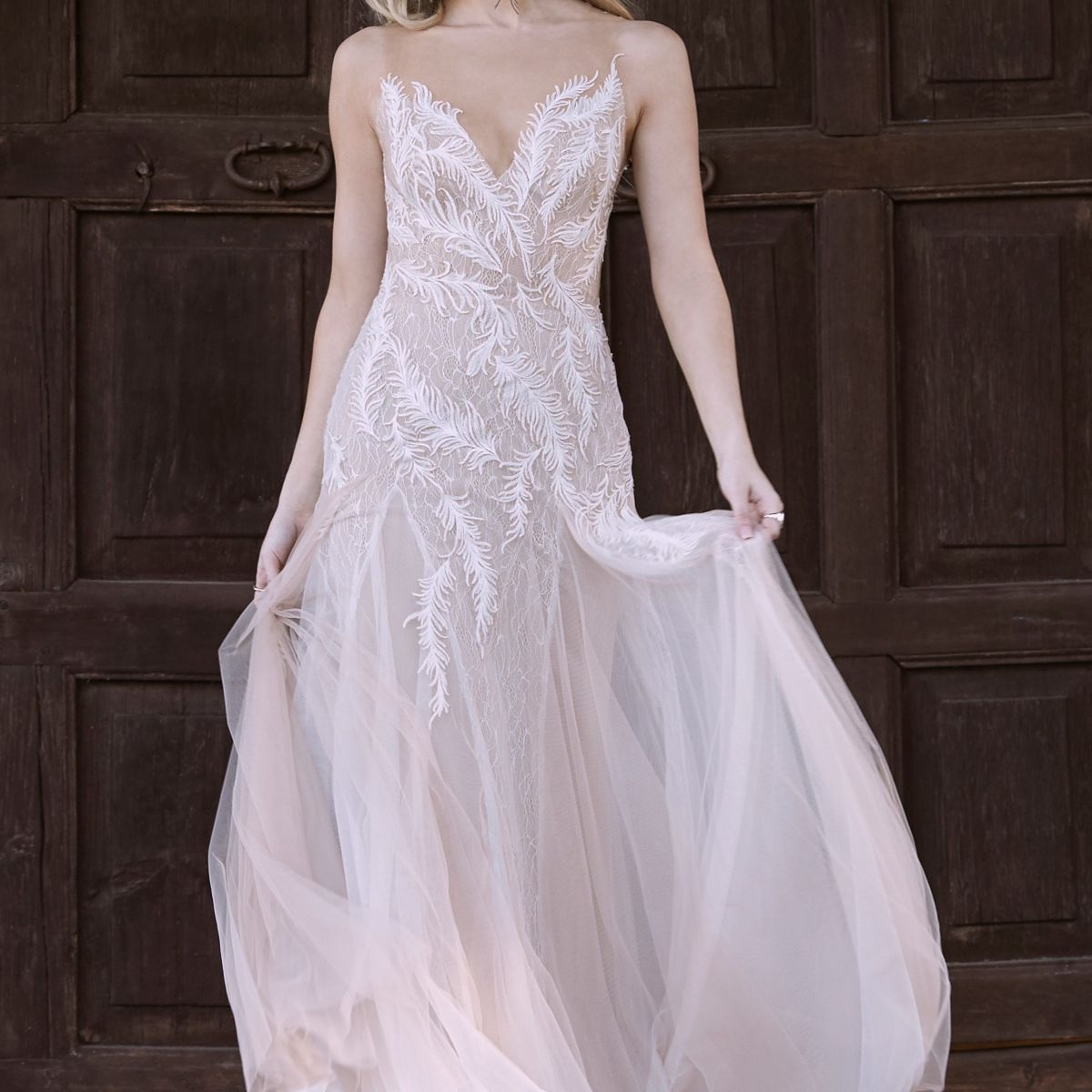 Model in a V-neck fit-and-flare tulle gown with feather embroidery