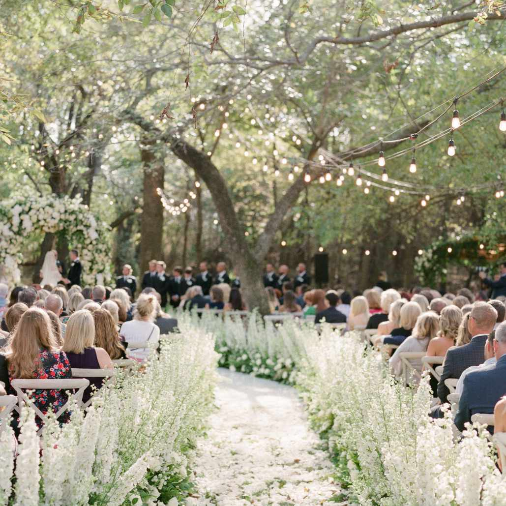 Flower and string light lined aisle