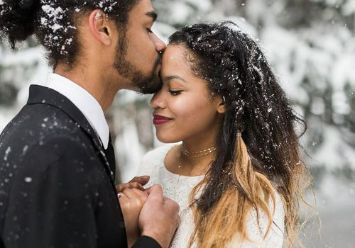 Groom kissing his bride's forehead outside in the snow