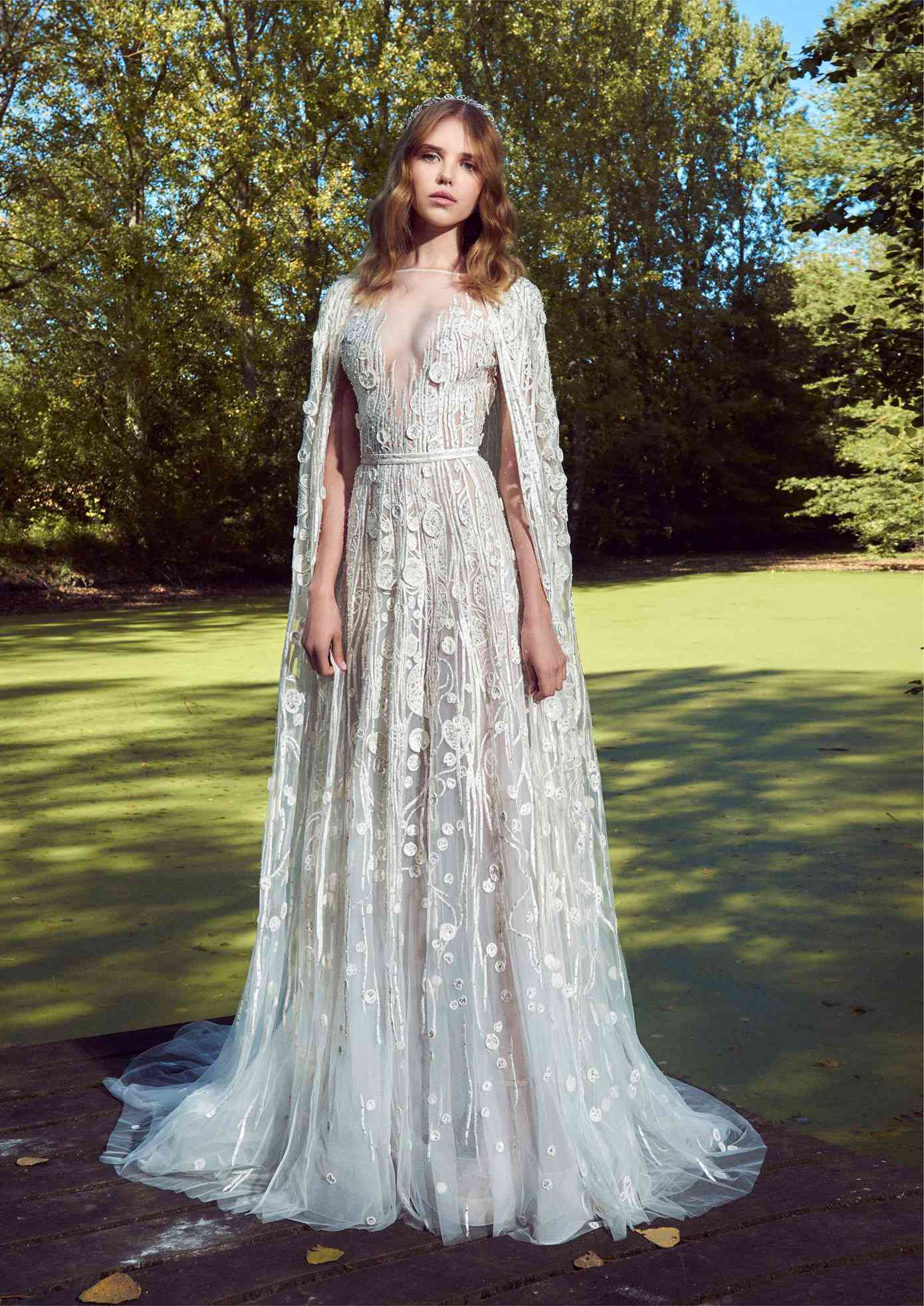 Model in a short-sleeve boat-neck A-line gown with an illusion neckline, beaded embroidery and appliques with a matching floor-length cape