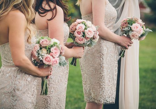 bridesmaids lined up in short neutral dresses holding bouquets