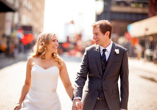 Bride (left) and groom holding hands while walking and smiling at each other