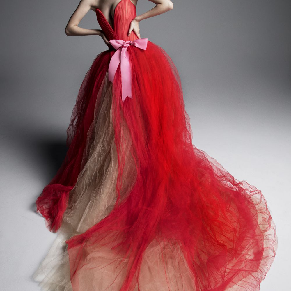 Model in red tulle ballgown with a plunging V-neck, a pink bow detail at the waist and a nude tulle underskirt