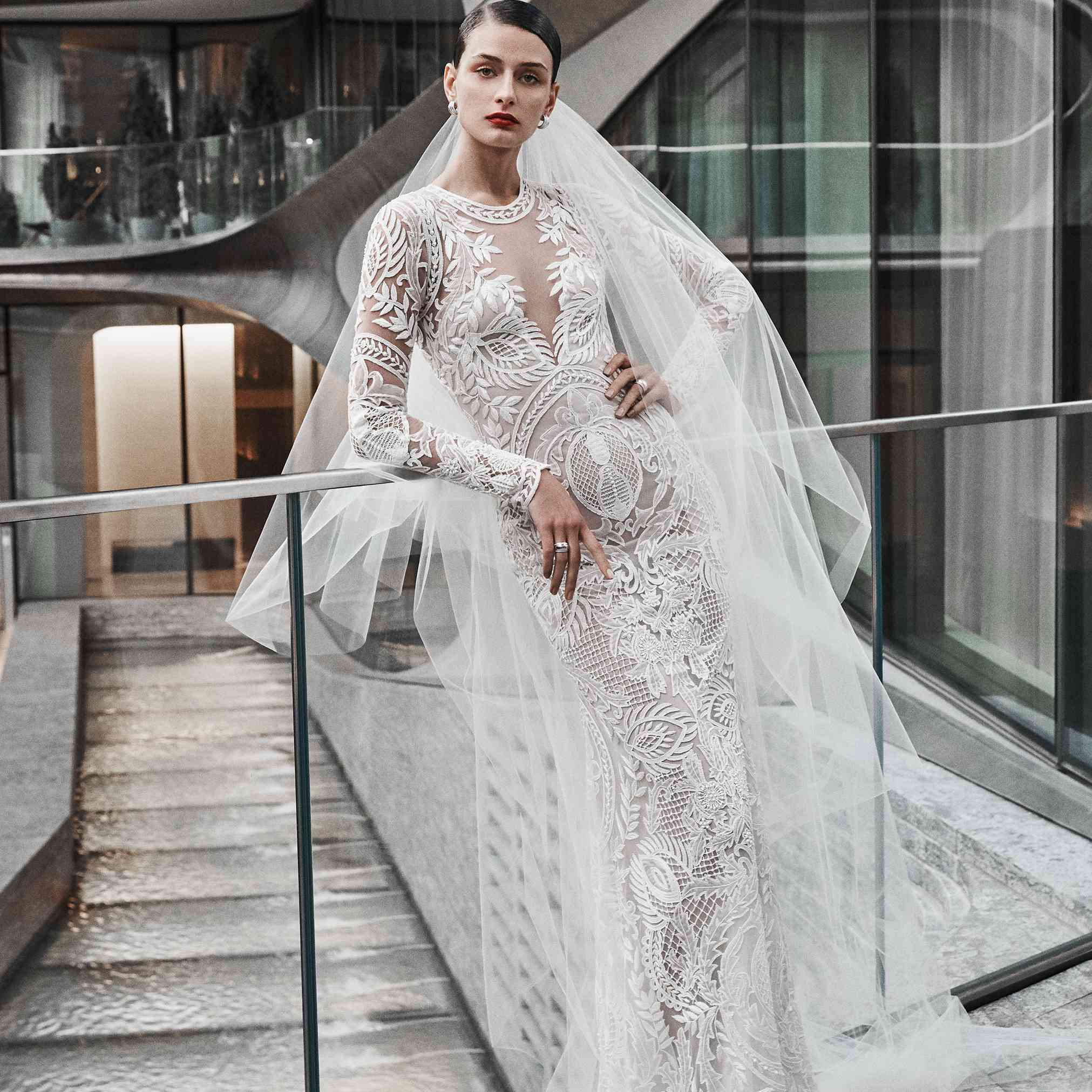 Model in long-sleeve embroidered gown with illusion neckline