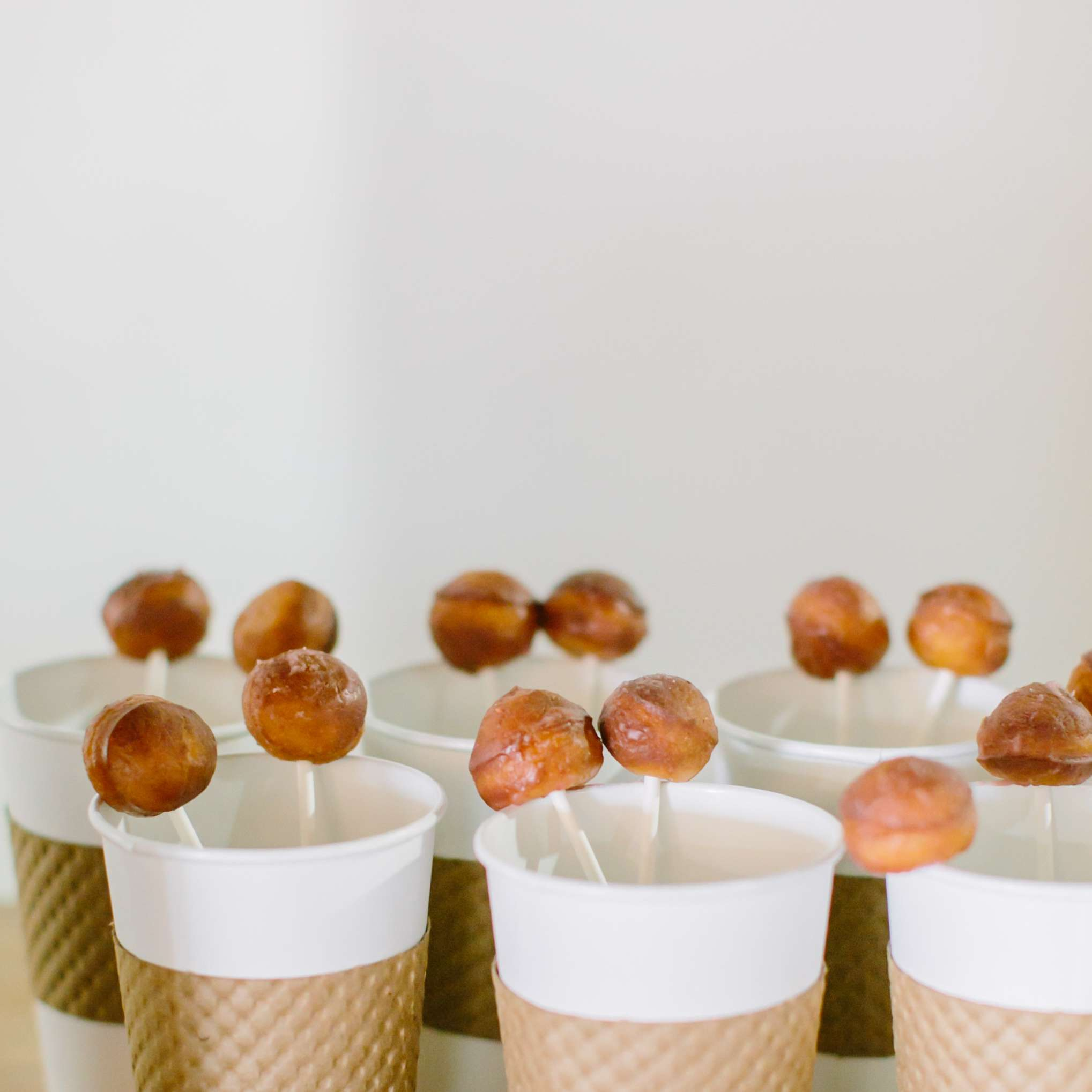 Coffee cups with donut holes on a stick