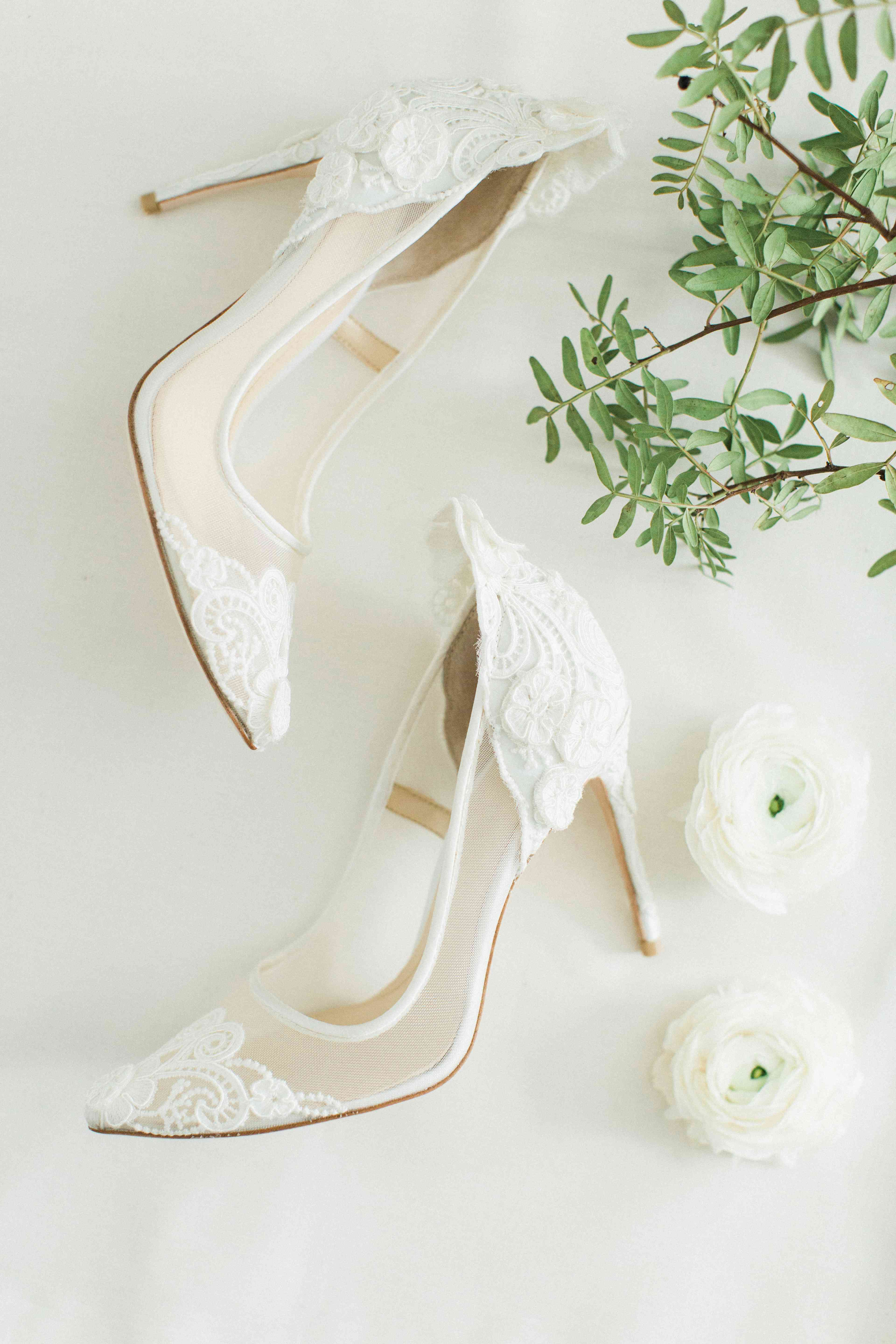 A pair of of white lace pumps.