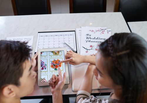 Couple choosing bouquet on tablet while wedding planning