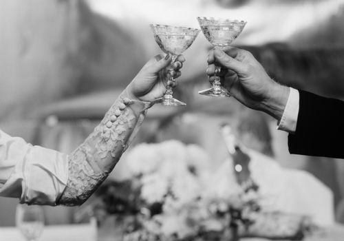 HANDS & ARMS OF A BRIDE AND GROOM TOASTING WITH CHAMPAGNE GLASSES (Photo by H. Armstrong Roberts/ClassicStock/Getty Images)