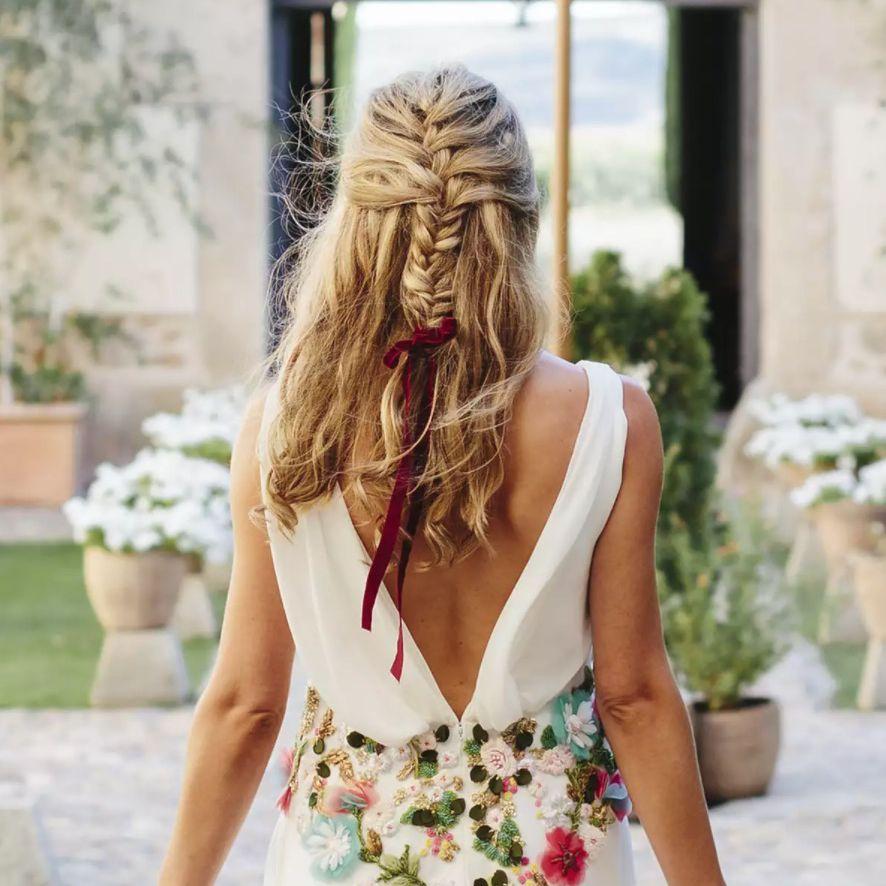 Bride walking away with braided hair in ribbon