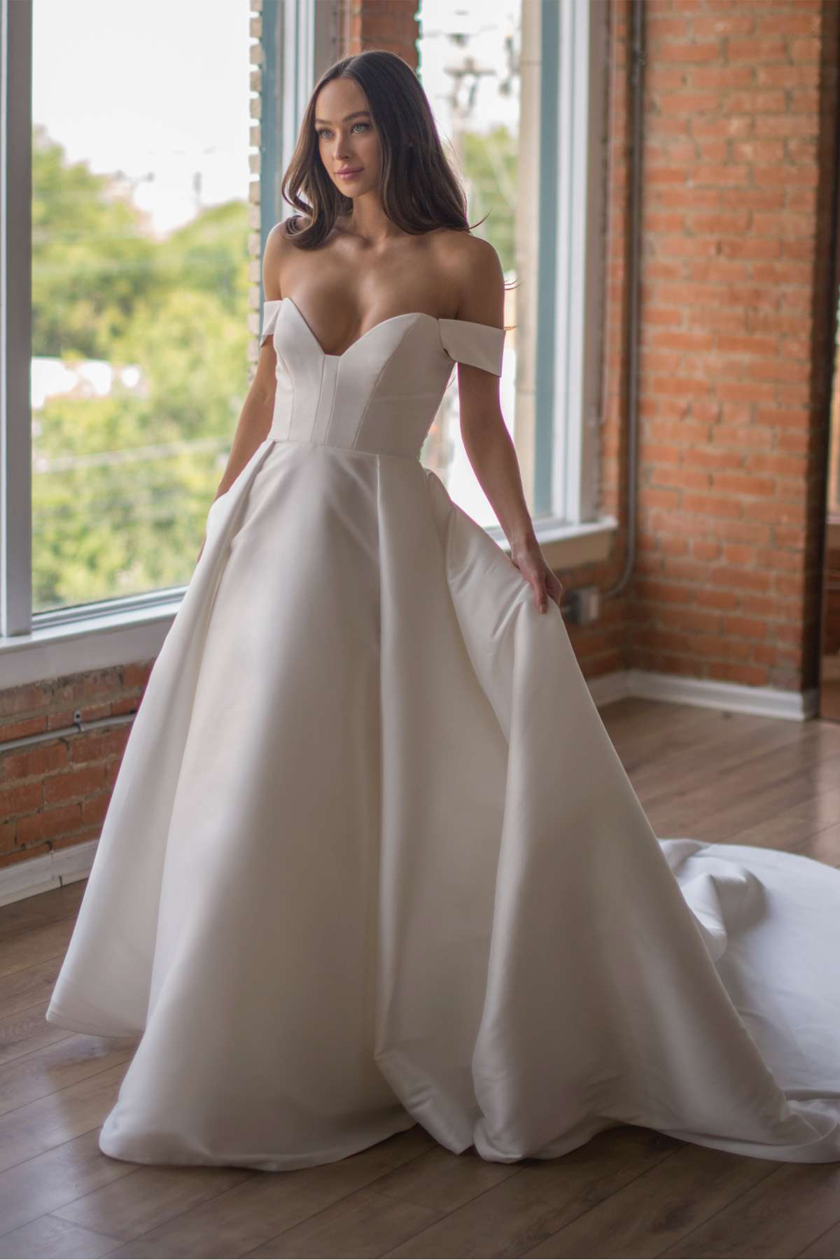 Model in a mikado ballgown with a deep sweetheart neckline and off-the-shoulder sleeves