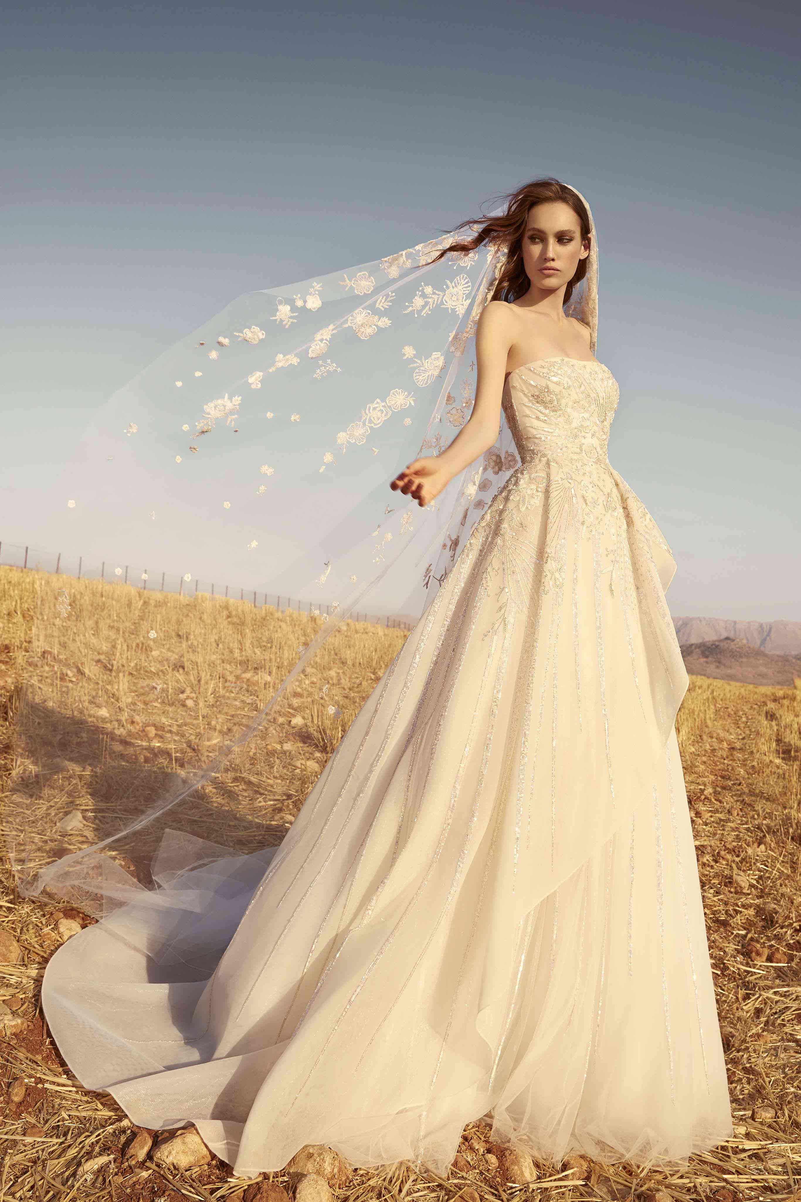Model in a strapless, layered, flared fully beaded sand-colored tulle dress with a matching veil