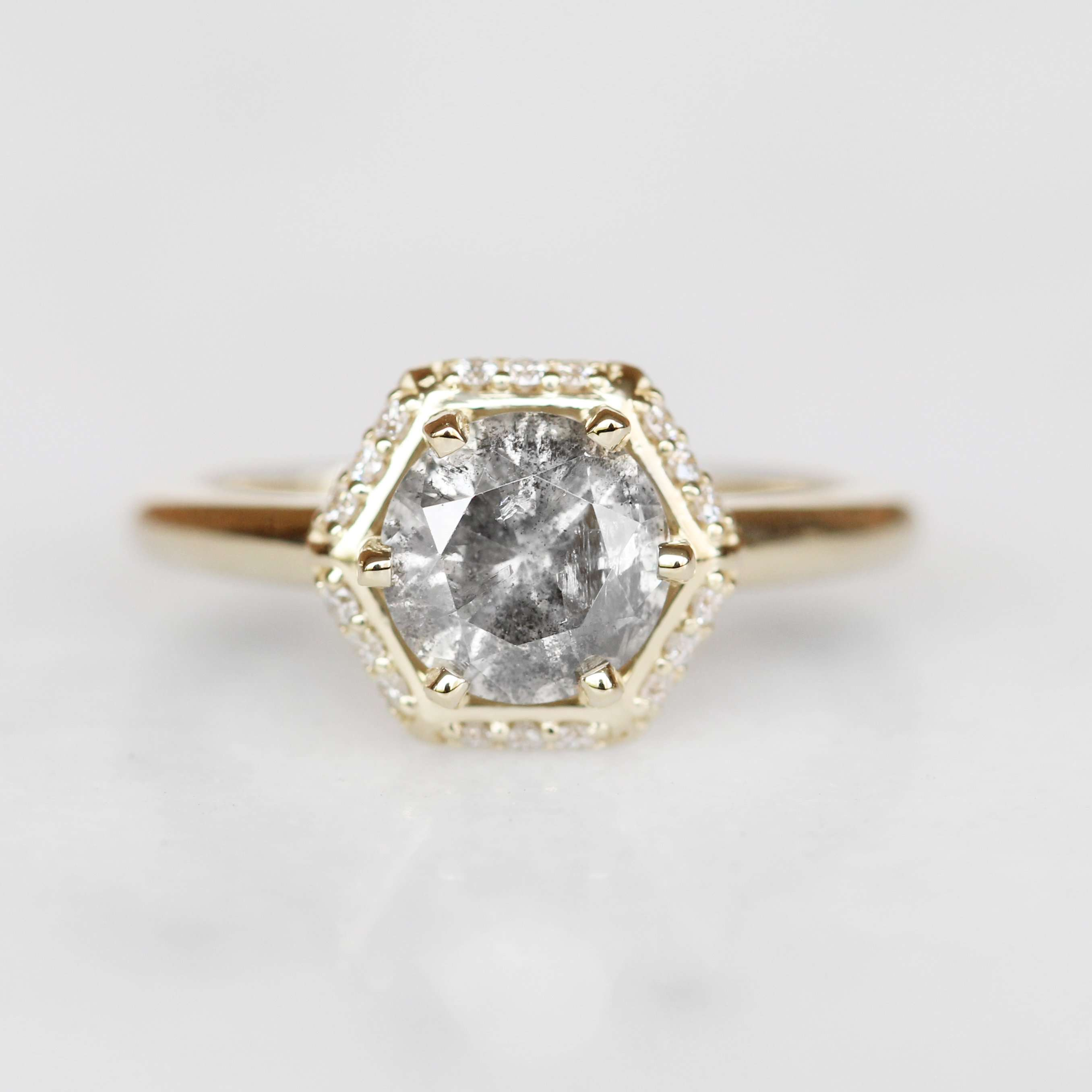 Natural round diamond in a hexagon-shaped diamond halo with a yellow gold setting