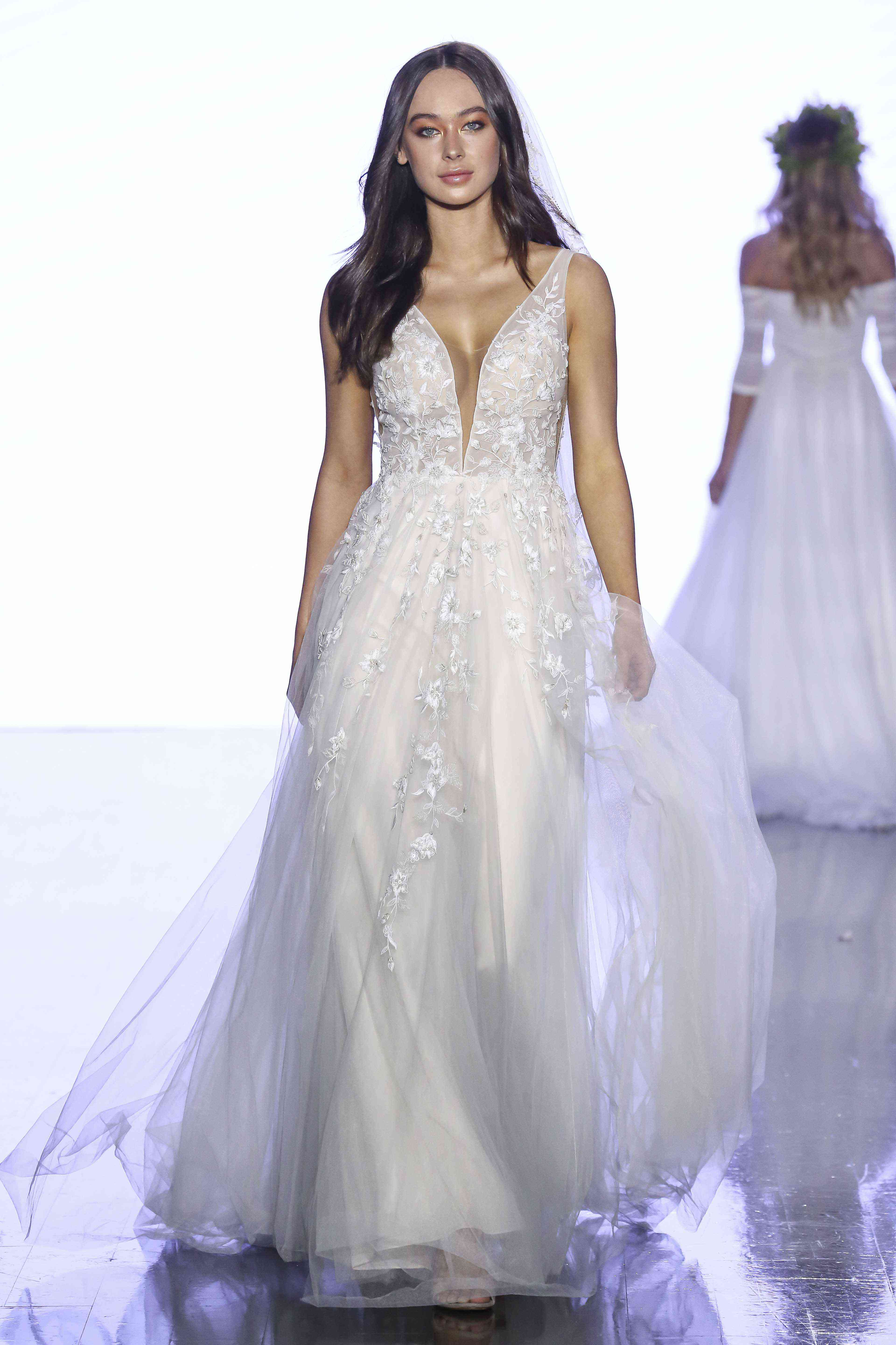 Model in tulle A-line gown with plunging neckline and floral embroidery