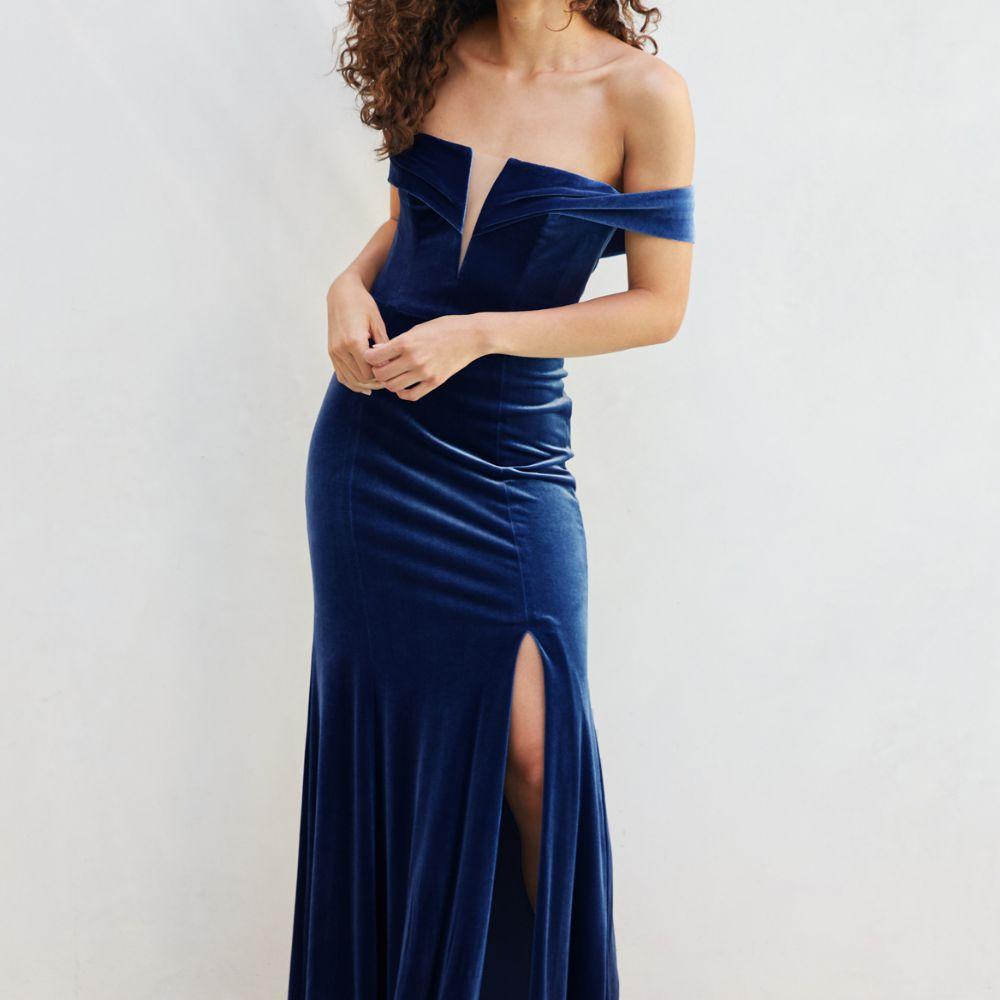 Model in a royal blue velvet off-shoulder gown with a plunging neckline and skirt slit