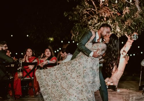 Bride and groom kissing as they have their first dance at an outdoor, evening wedding
