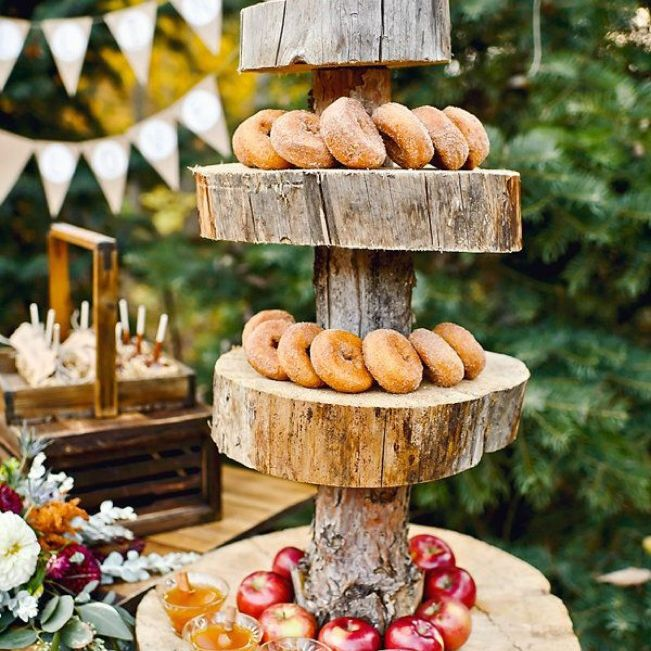 Tiered wooden display with donuts, apples, and cider