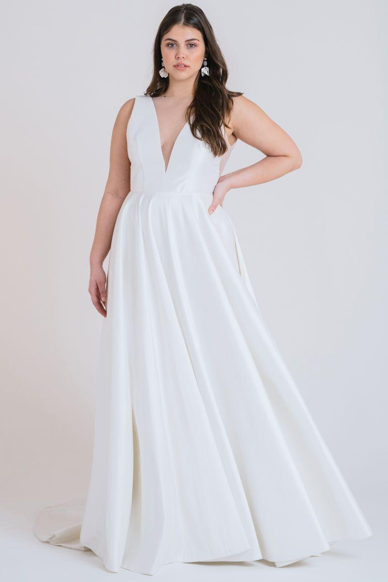 Plus size model in v-neck satin wedding gown