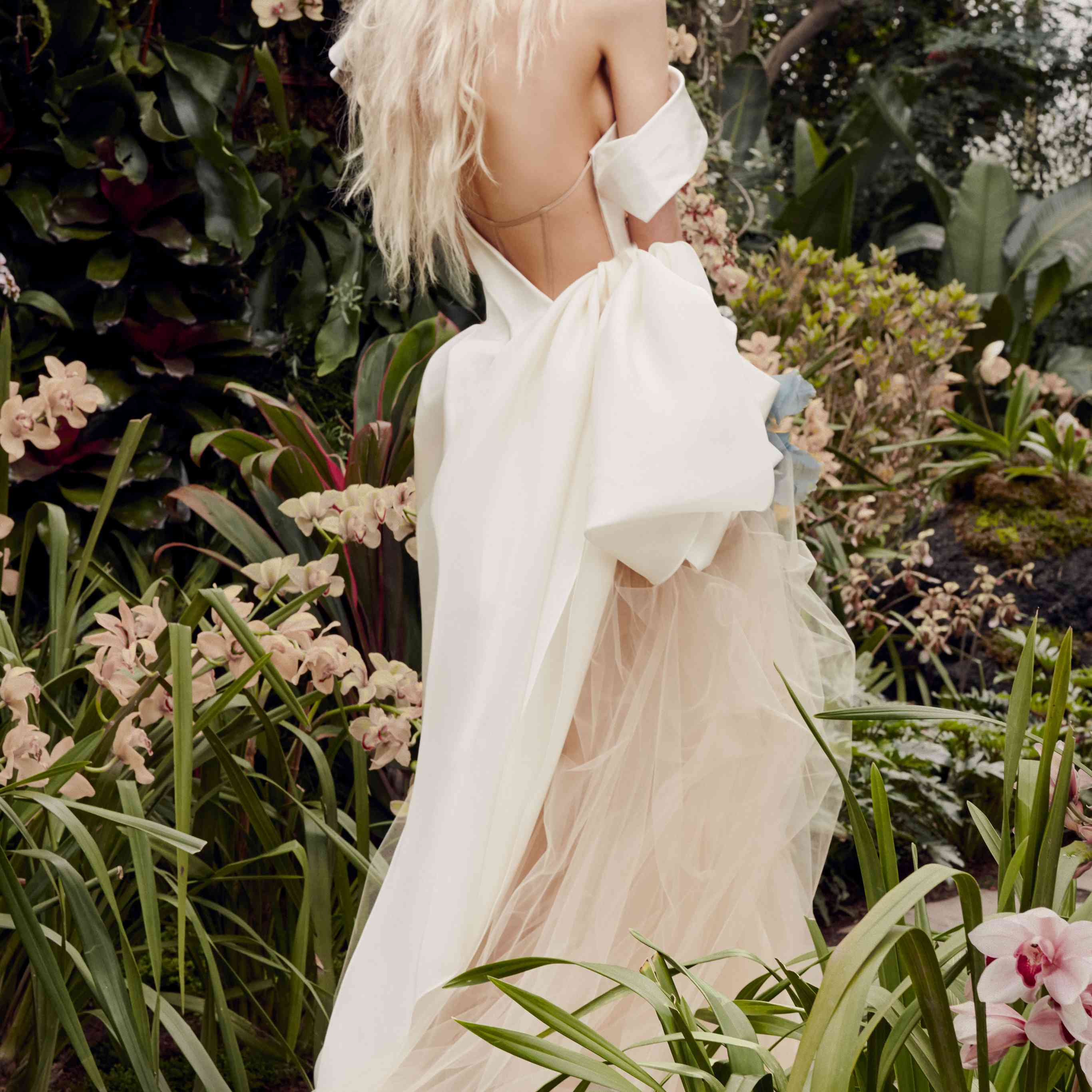 Model in a white one-shoulder gown with nude tulle exposed skirt