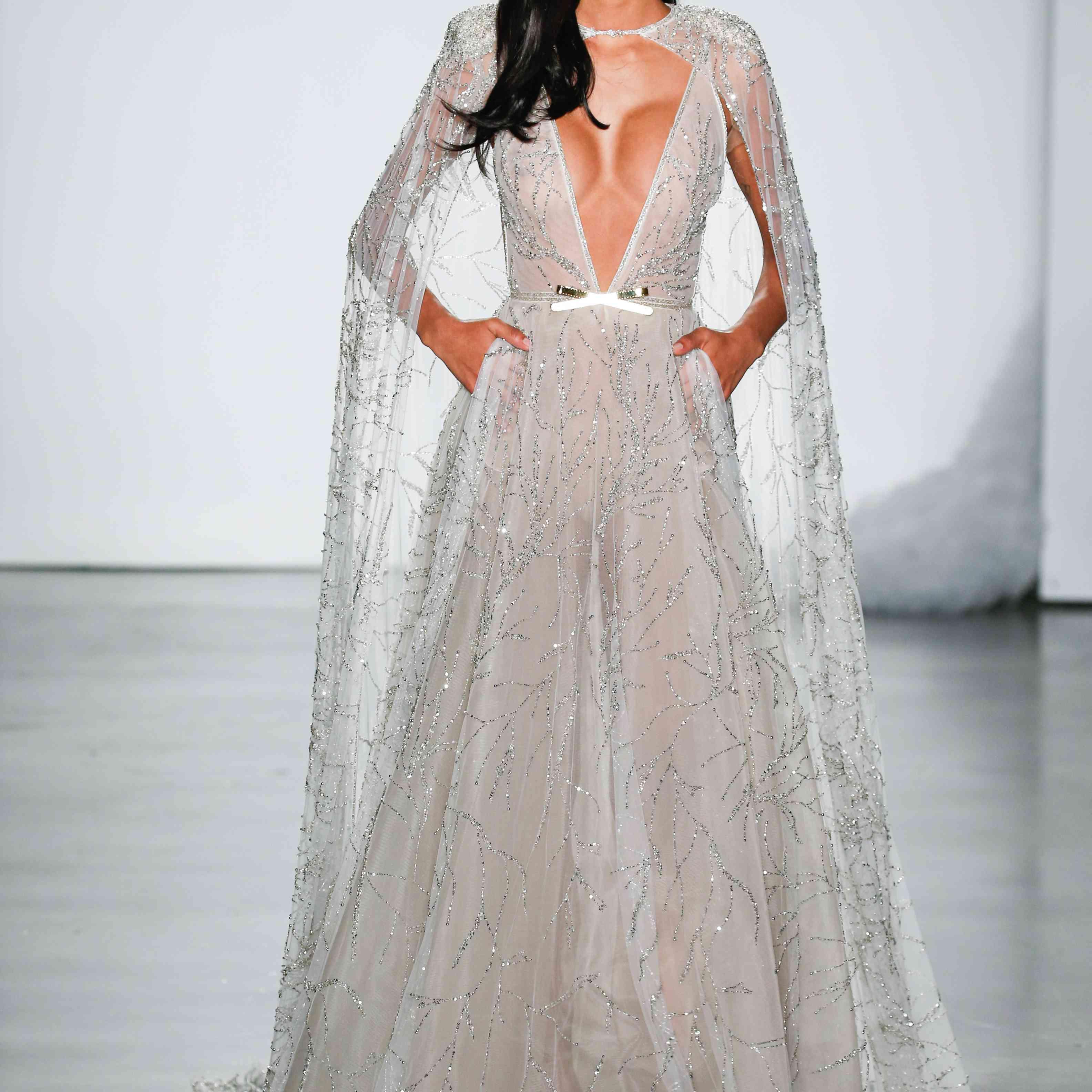 Model in deep V-cut wedding dress with cape