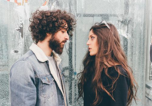 Young man and woman, standing face to face, pensive expressions