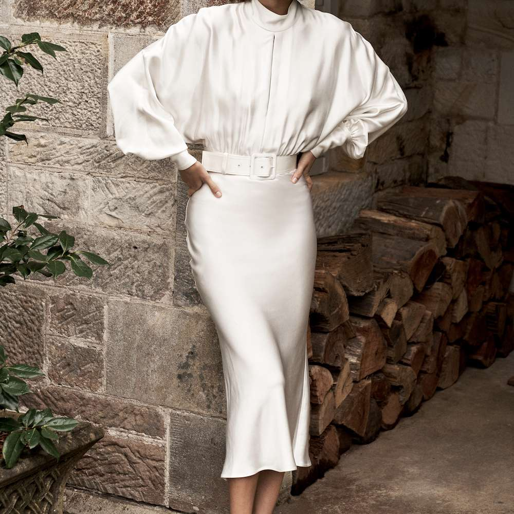 Model wearing Rebecca Vallance belted Florent Midi wedding dress in white silk with high neck and dramatic sleeves