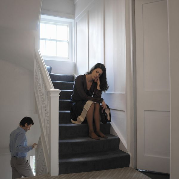Woman sitting on stair way, man descending lower level