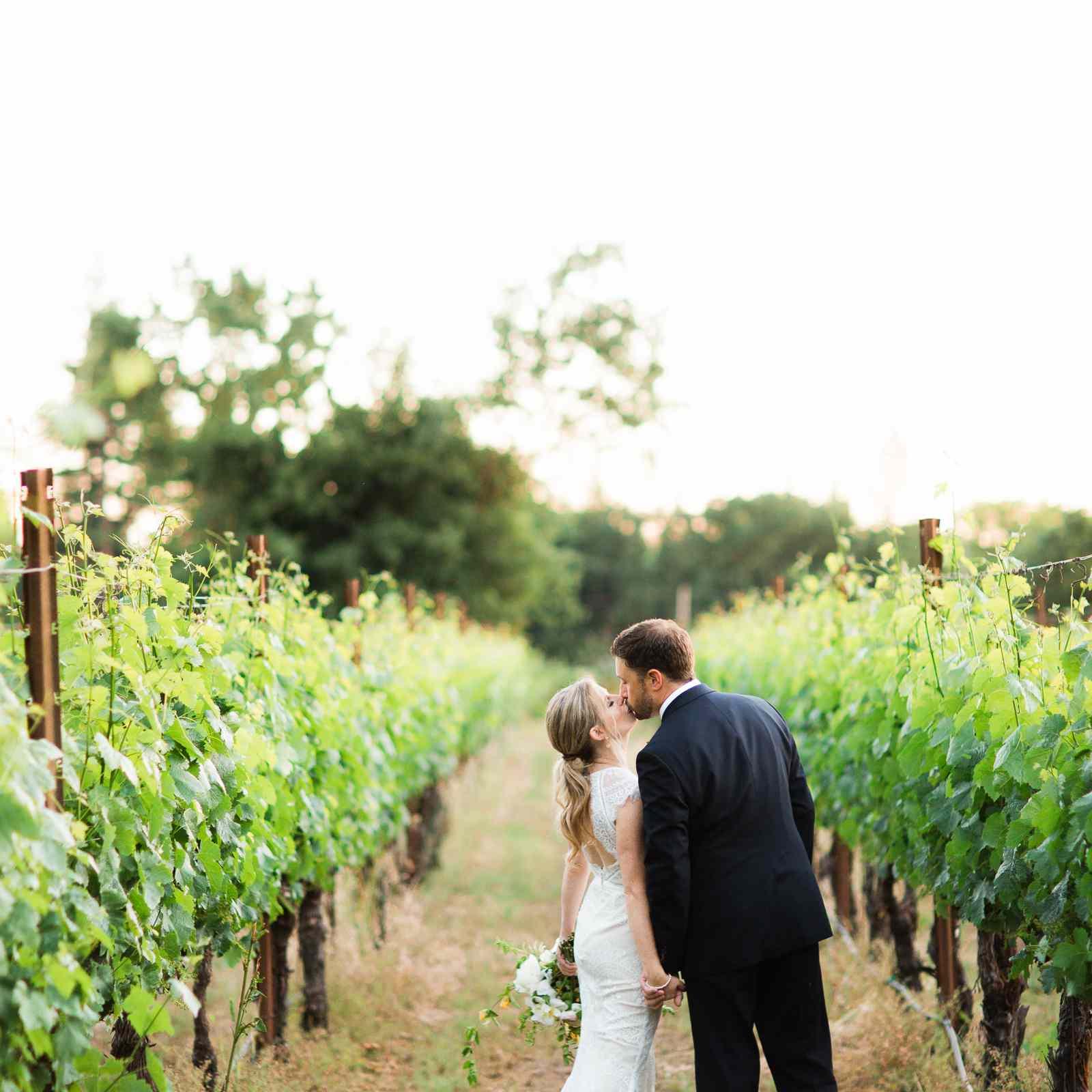 A couple kissing at a vineyard