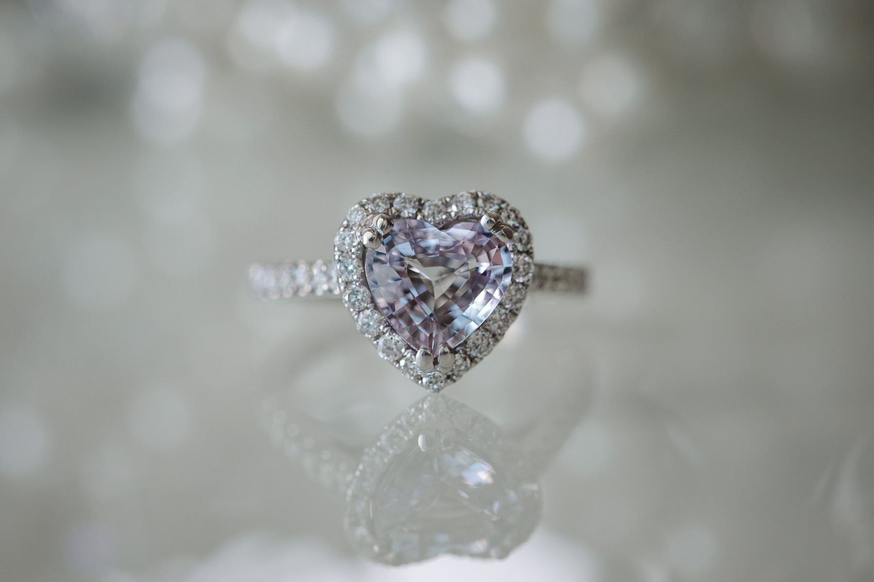 Heart-shaped engagement ring with diamond halo and diamond band