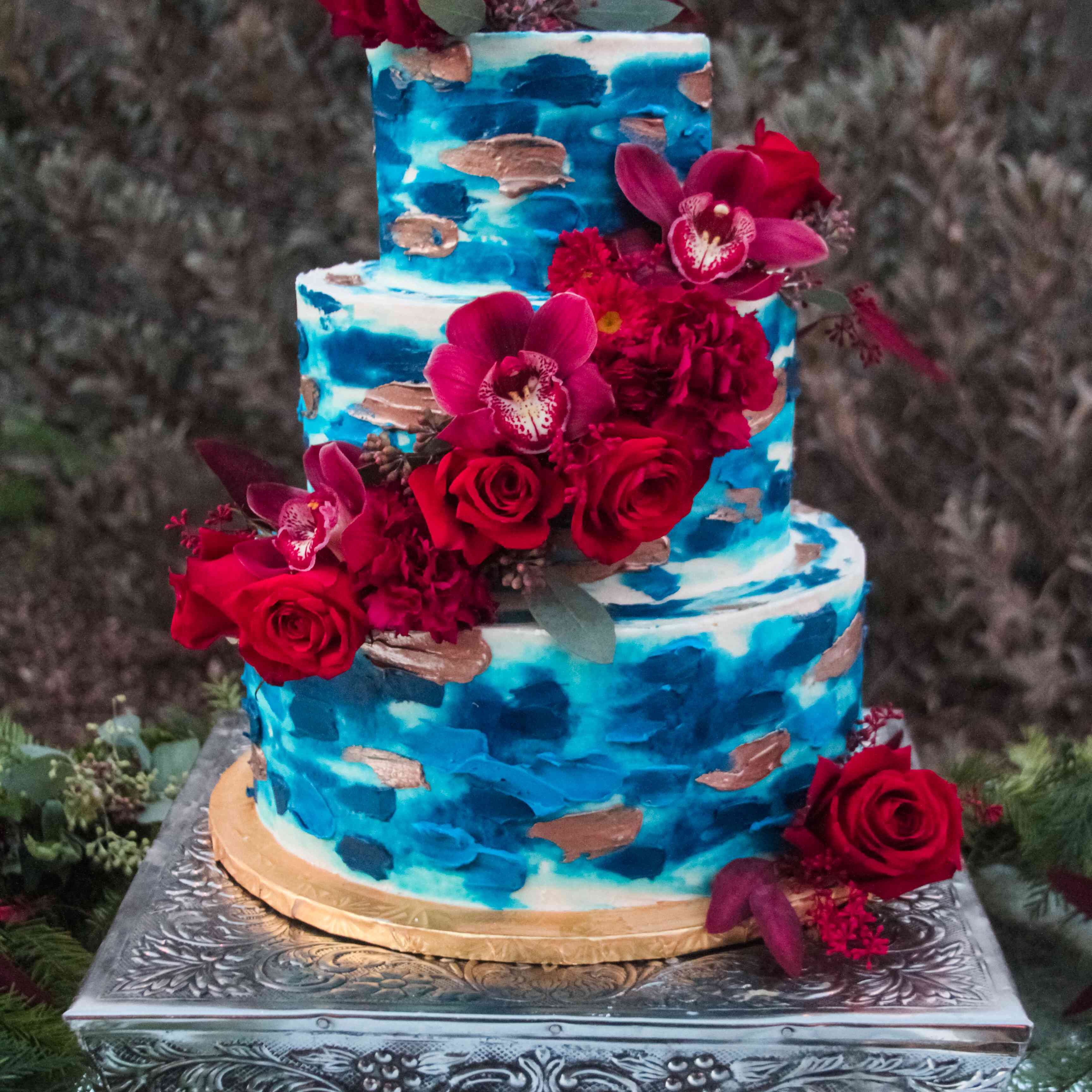 Vibrant Blue Wedding Cake with Red Flowers