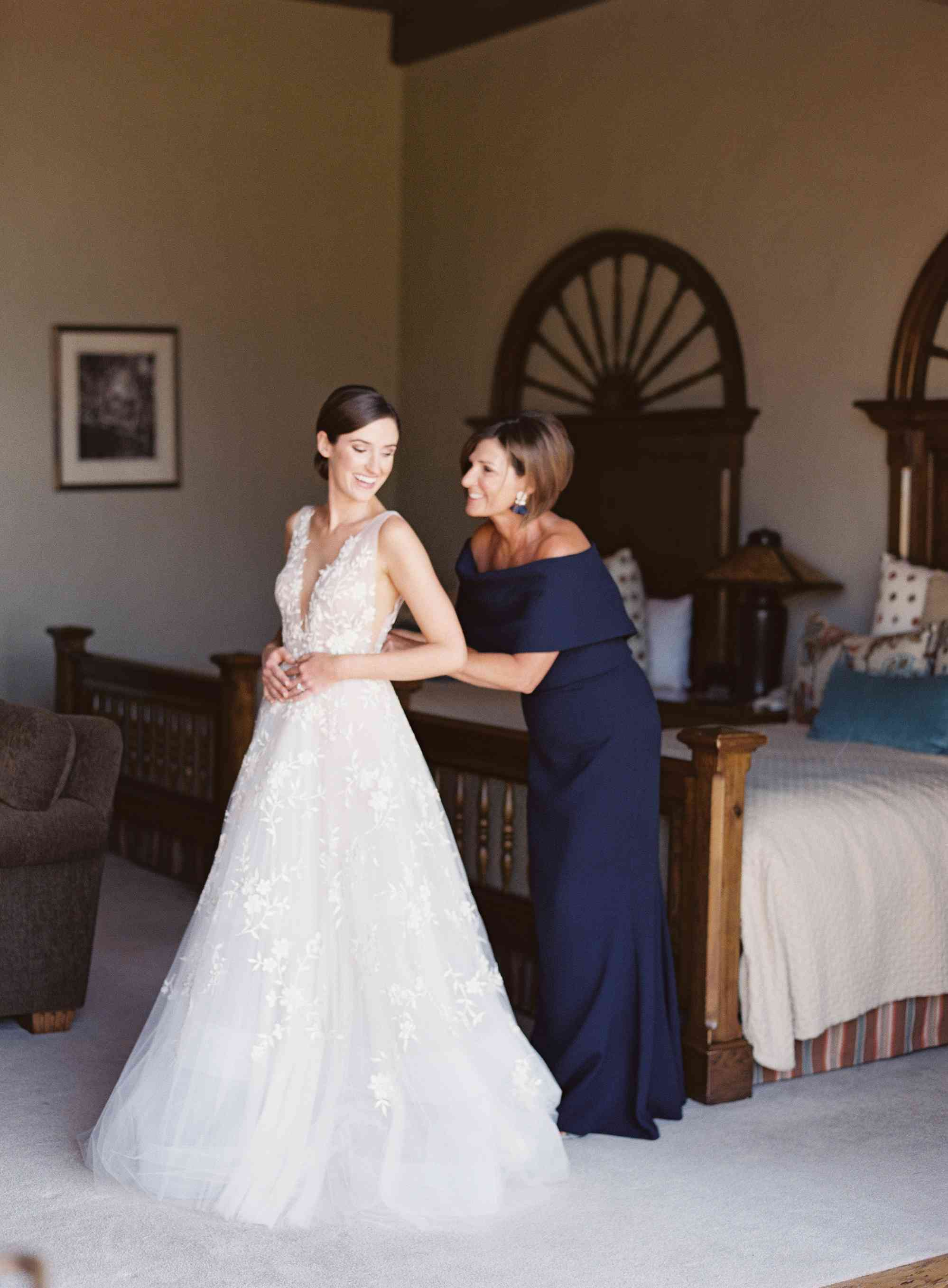 mother of the bride zipping wedding dress