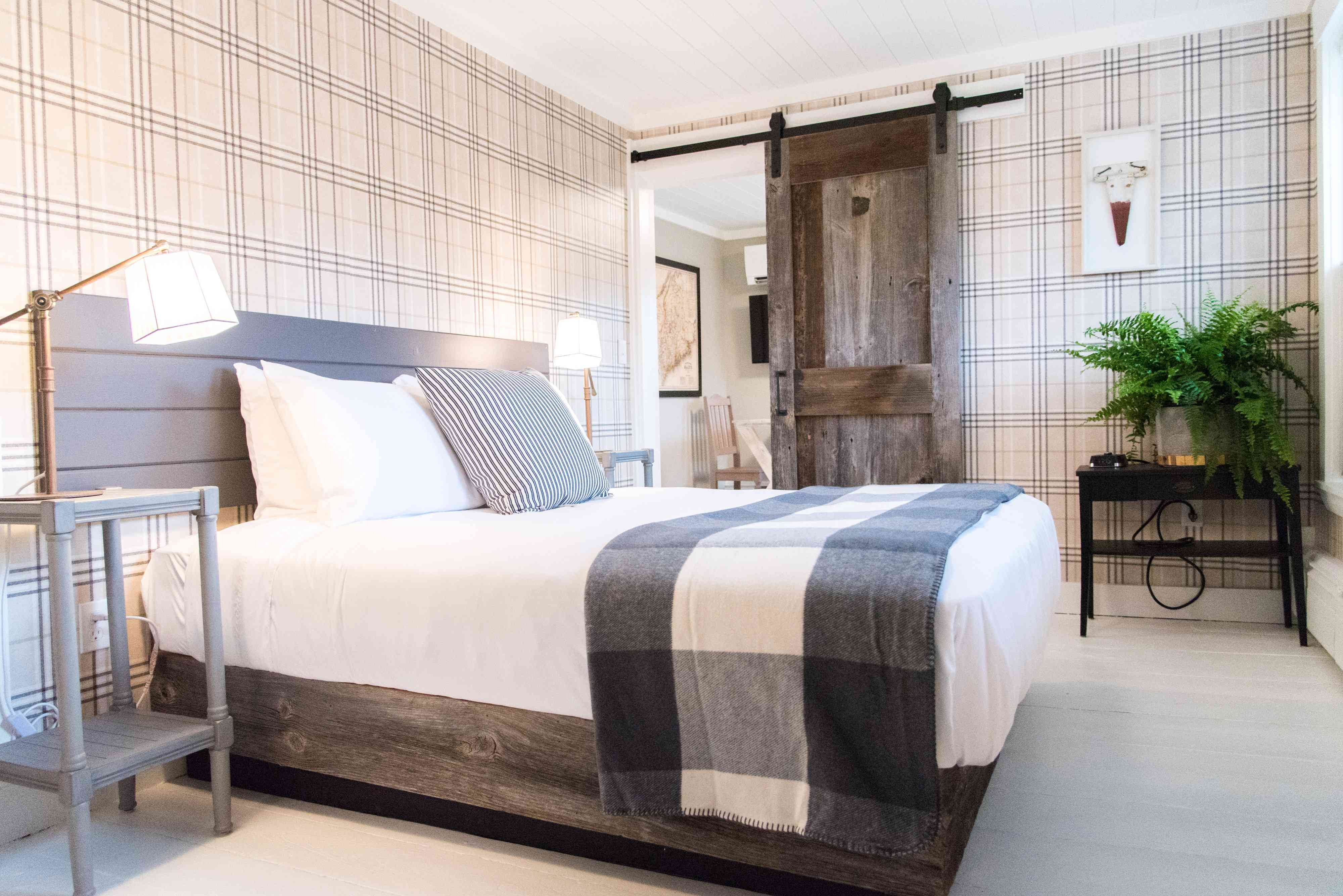 Hotel room with barnyard door and plaid wallpaper