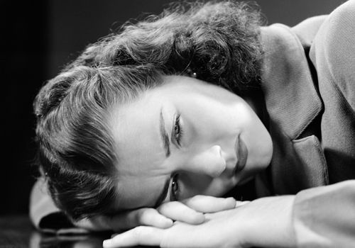 Sad young woman lying her head and hands on the surface of a table circa 1940s