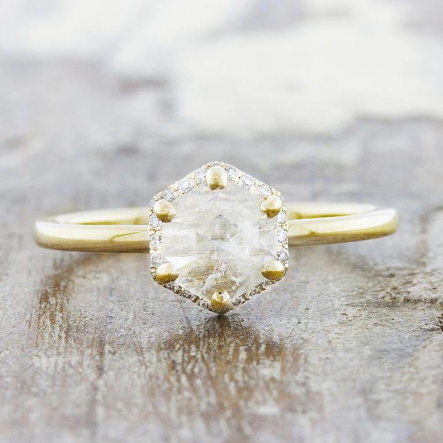 Rough hexagon-shaped diamond with diamond crown on yellow gold setting