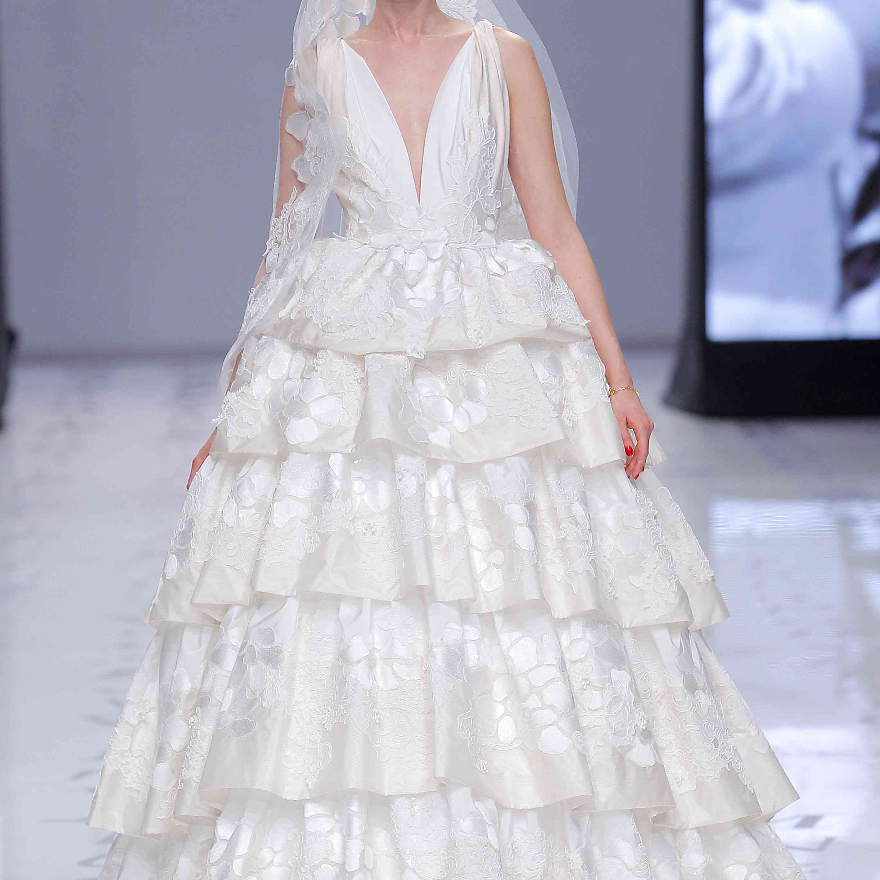 Model in a voluminous princess dress with a moiré skirt that features flower motifs and layers of ruffles and a deep V-neck bodice draped on the shoulders and decorated with embroidered lace