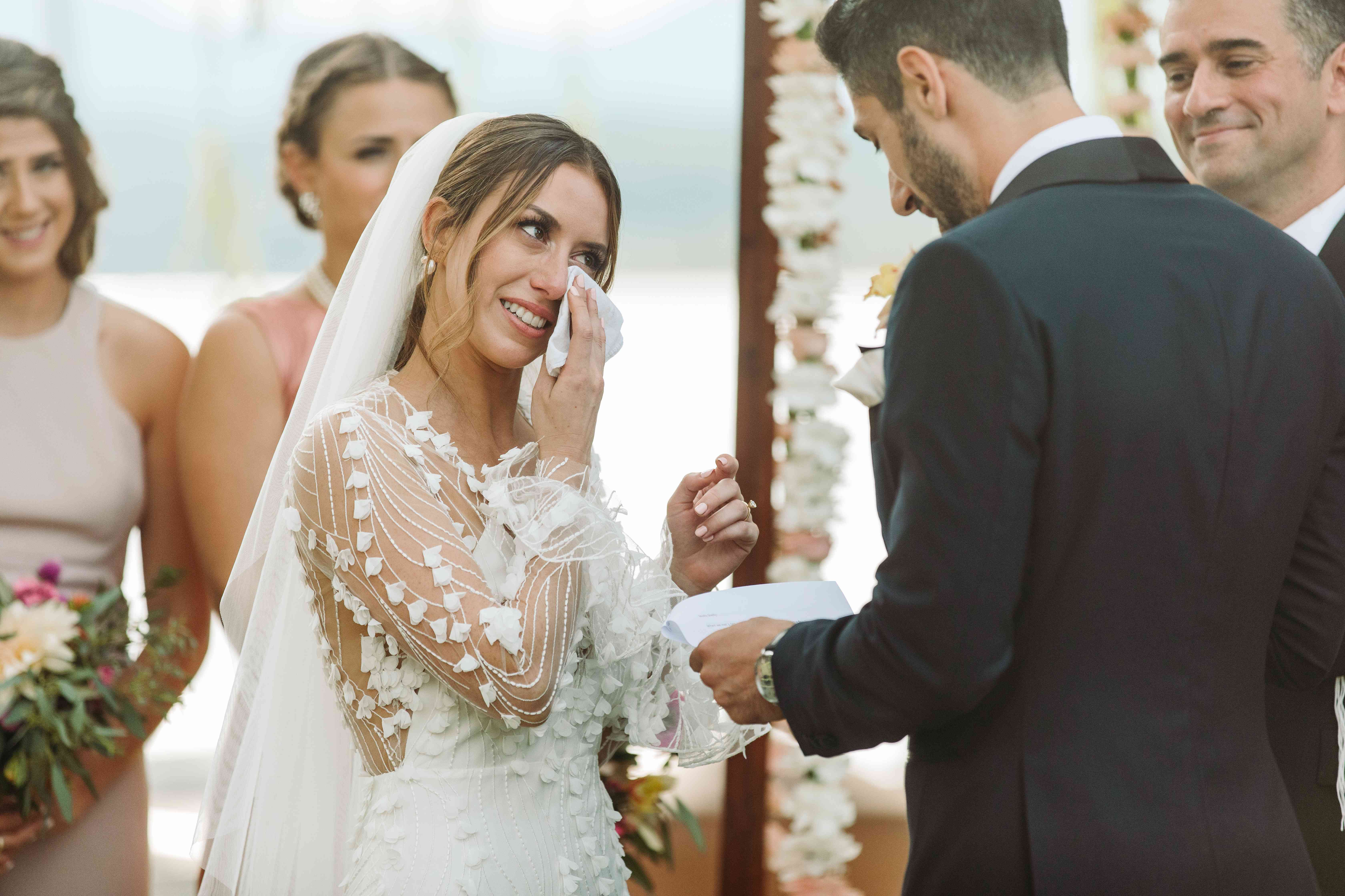 bride wiping tears during wedding ceremony