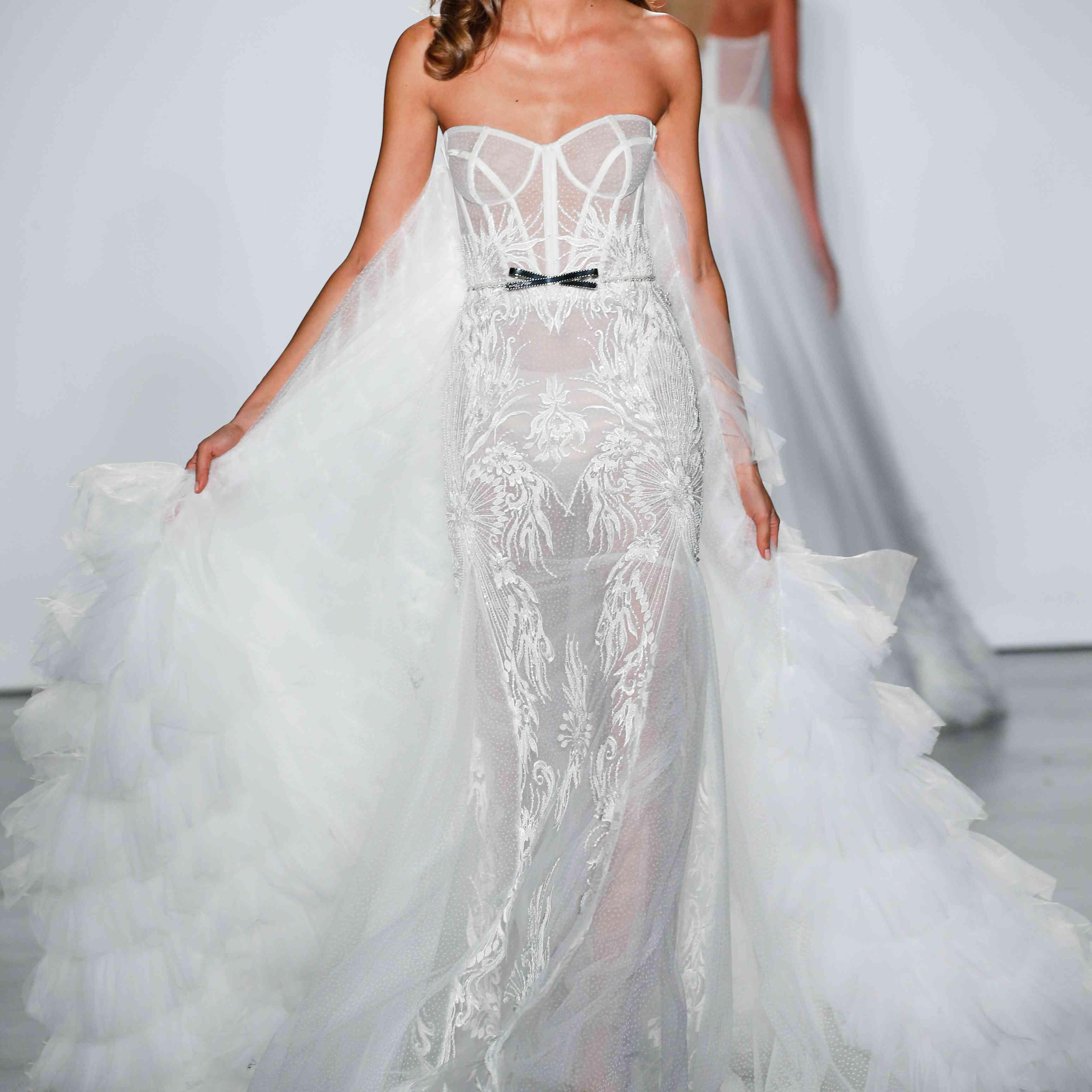 Model in Inbal Dror VIP wedding dress with tiered ruffle train