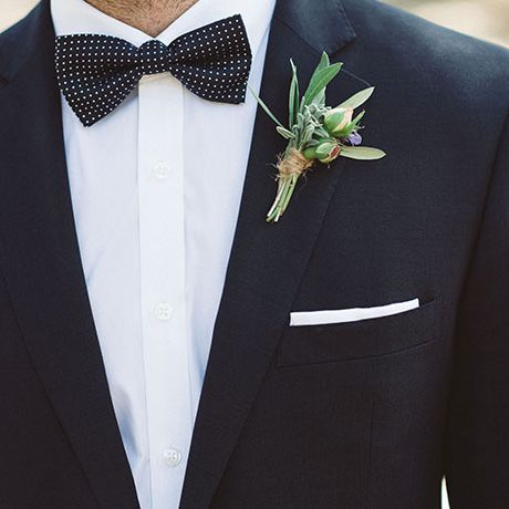 A simple boutonniere comprised of berry and gum leaves and additional greenery, created by Petal and Pod