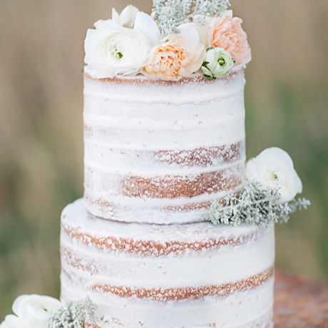 A thinly-frosted white wedding cake topped with pale petals by Angel Delights