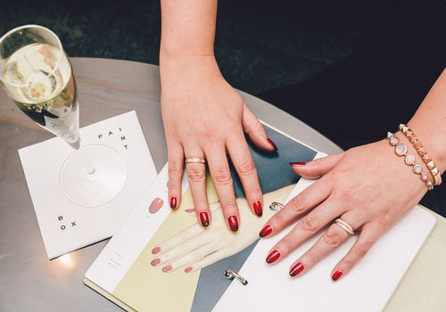 Women's hands with red nails and glass of champagne
