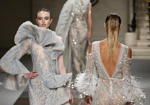 Three models walking down runway in couture wedding gowns