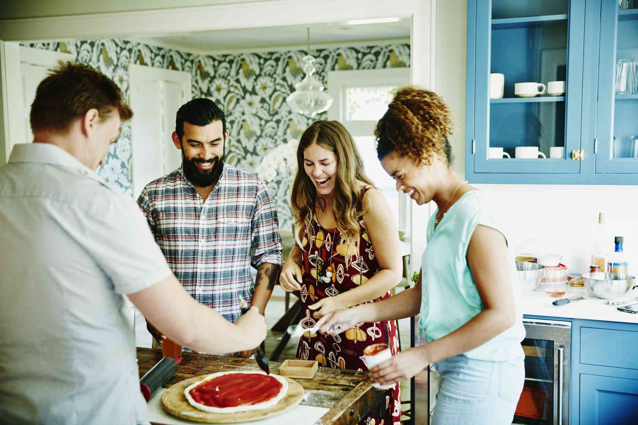 Laughing group of friends preparing pizza together in kitchen