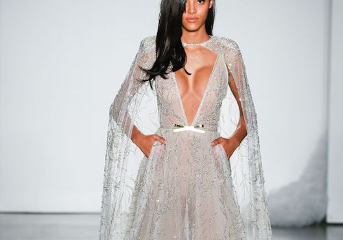 Model in plunging neckline wedding dress with cape
