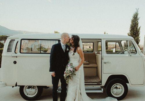 bride and groom in front of white vw bus
