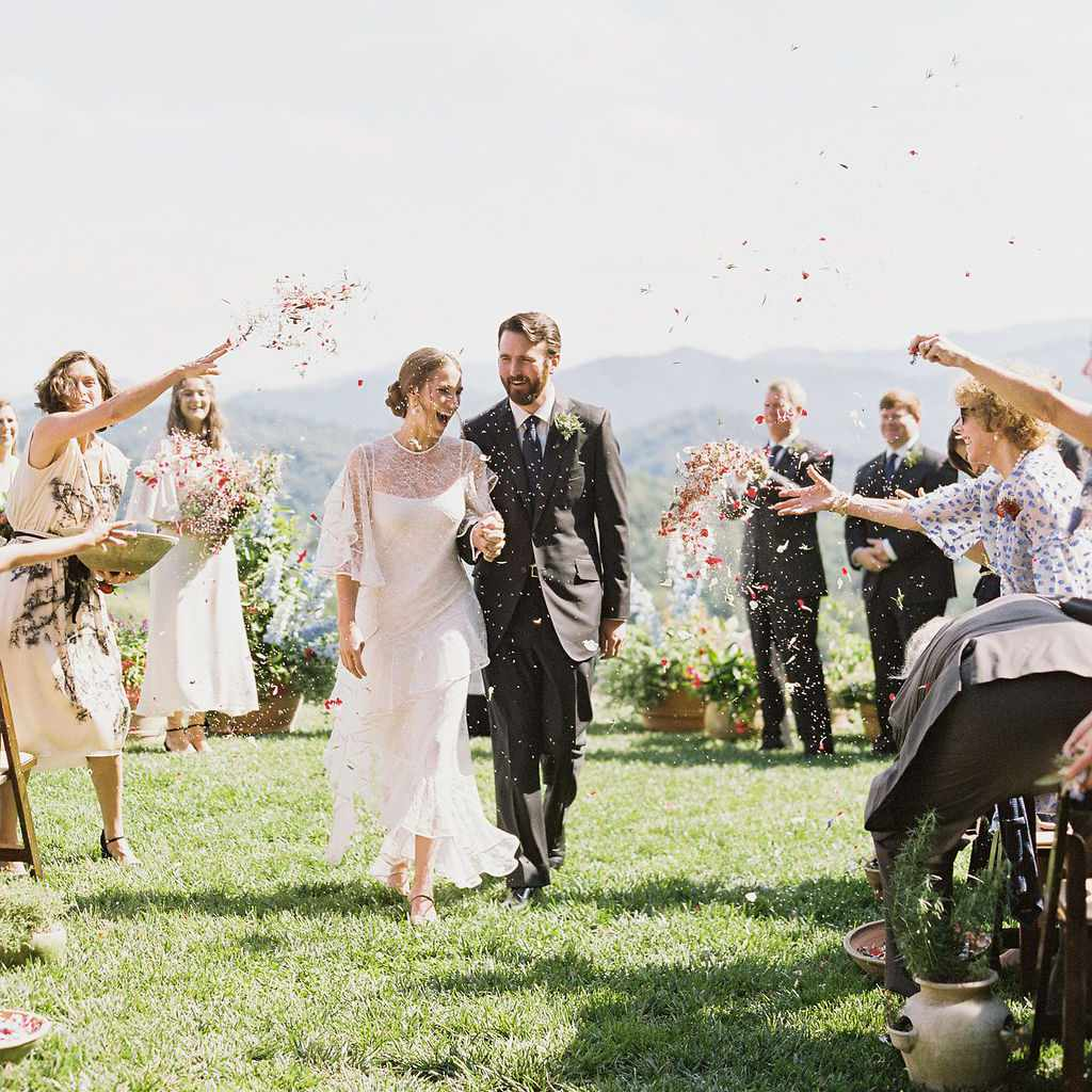Wedding guests tossing petals as bride and groom recess down the aisle