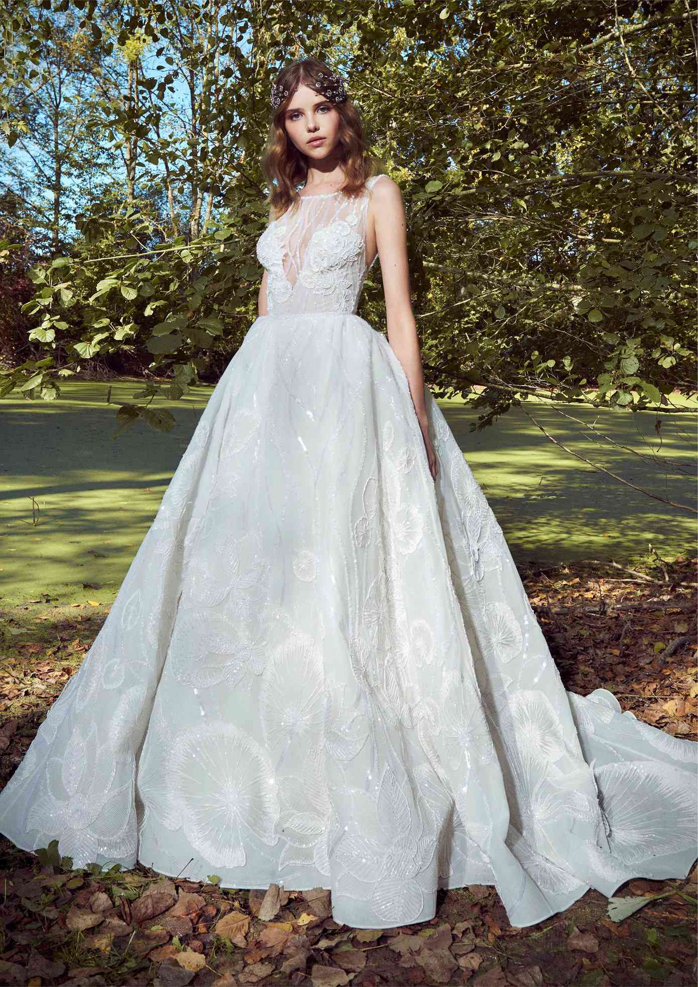 Model in a sleeveless ballgown with a beaded illusion neckline and allover sequined and beaded floral embroidery with appliques