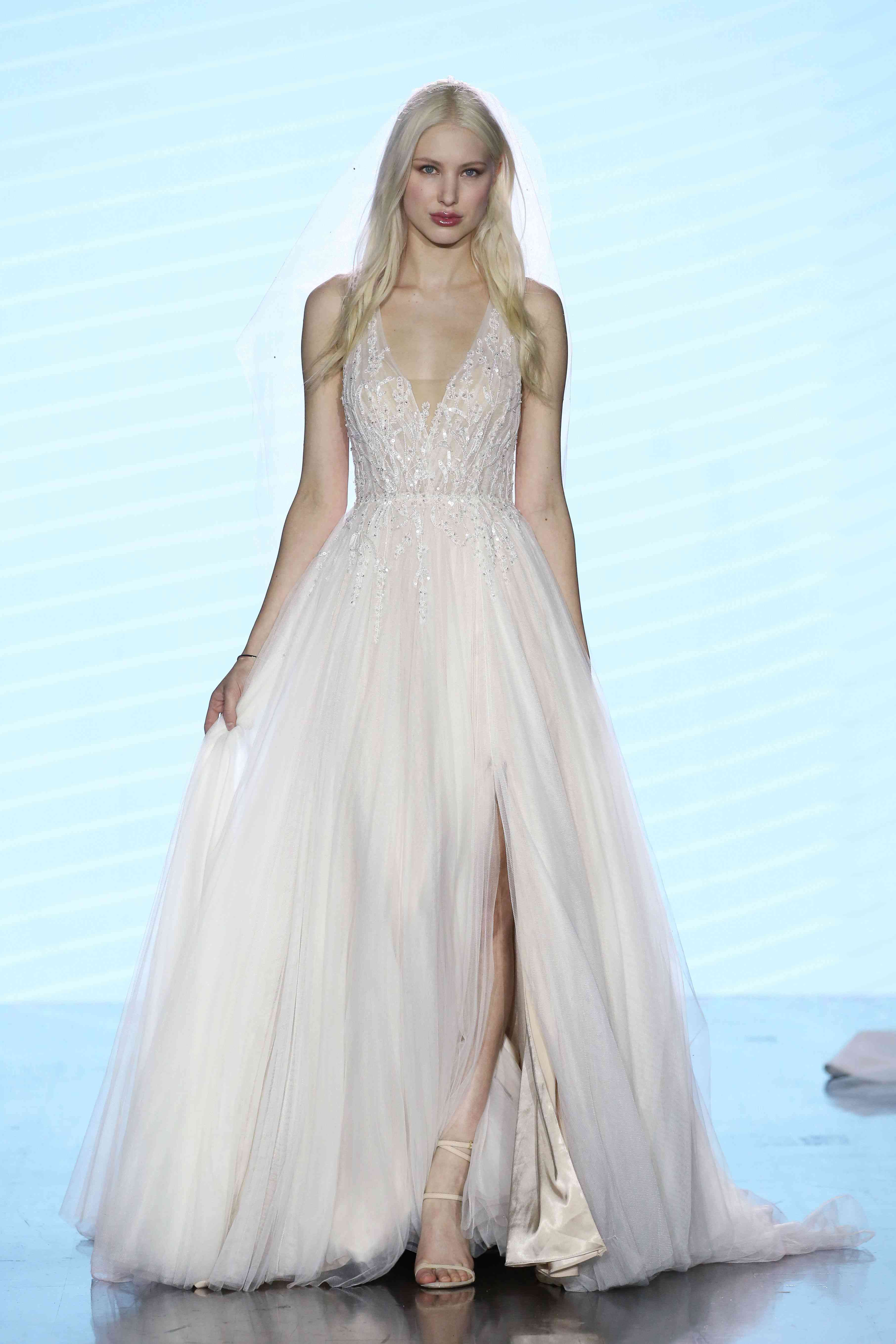 Model on runway in deep V-neck ballgown with a slit tulle skirt and beaded bodice