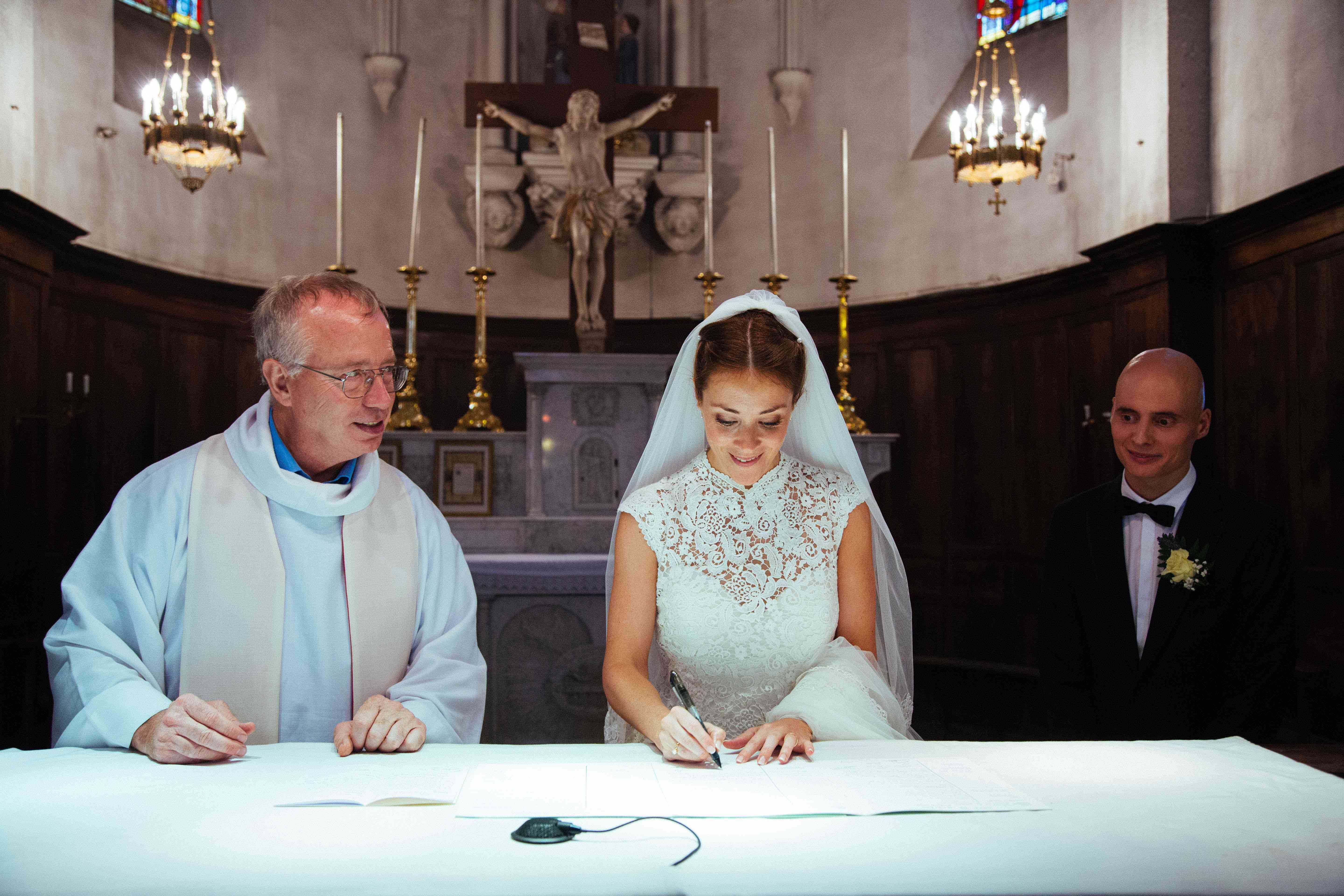 Bride signing document with priest