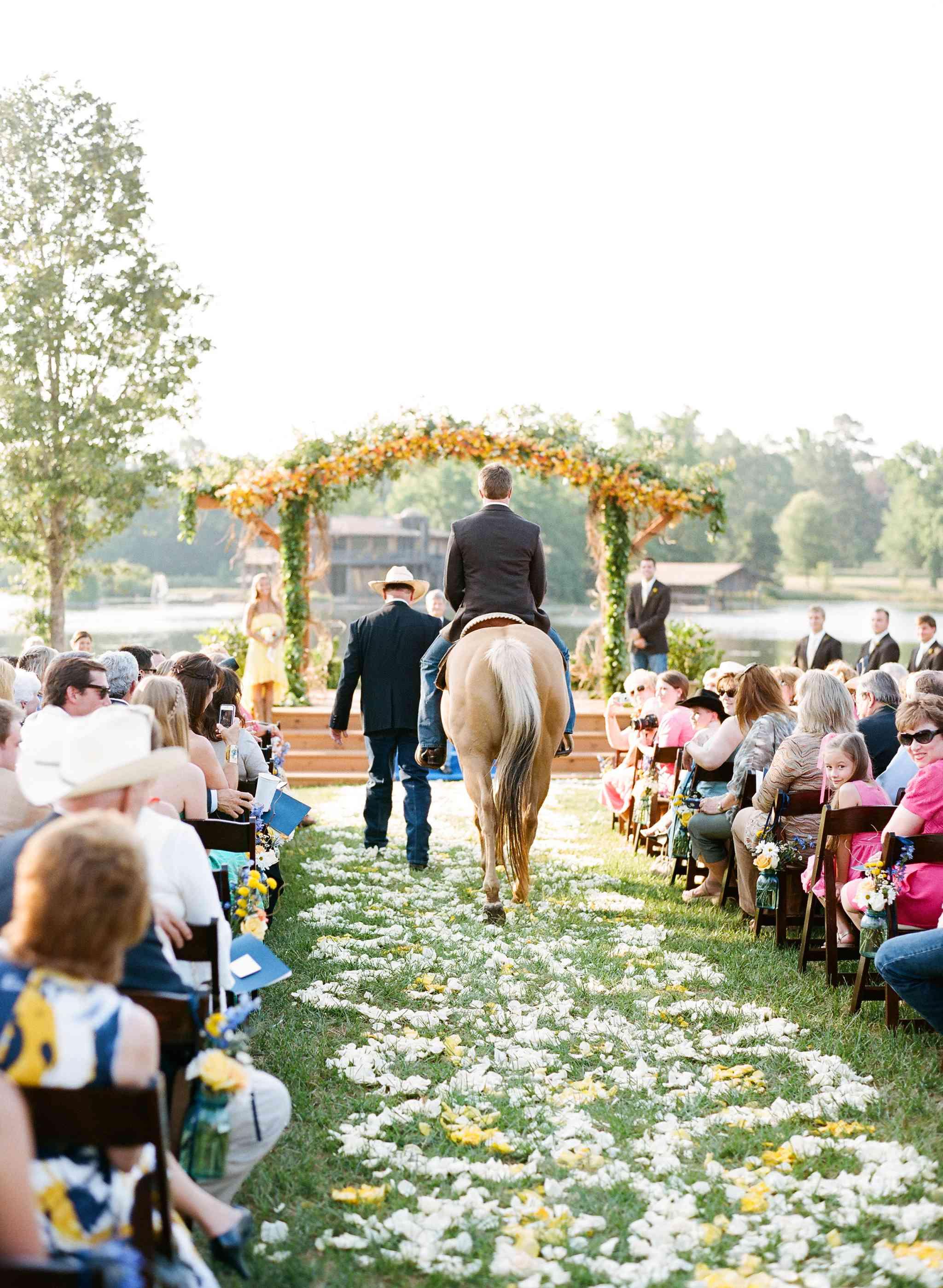Groom riding horse down aisle