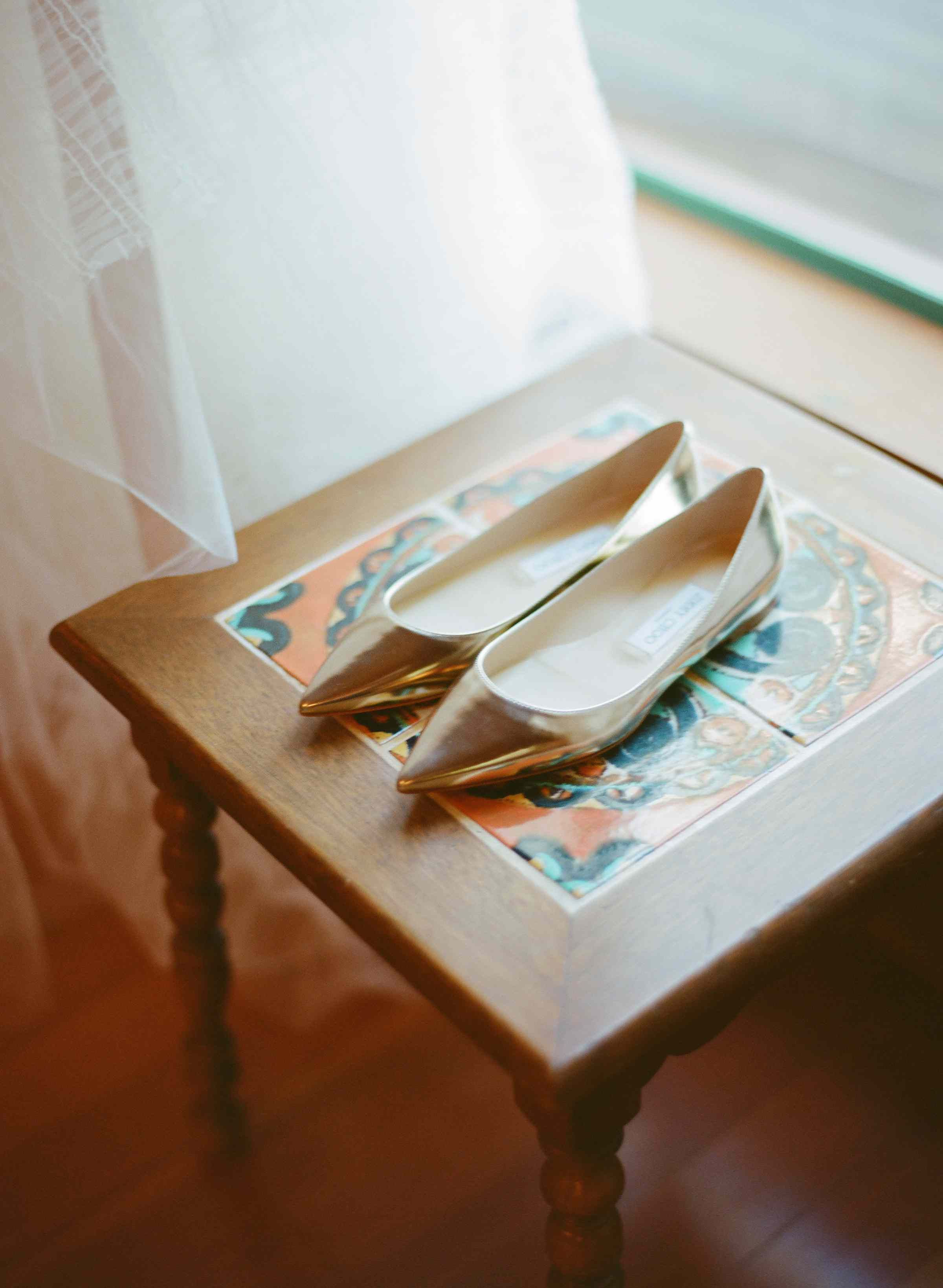 Pointed metallic flats sitting on table.
